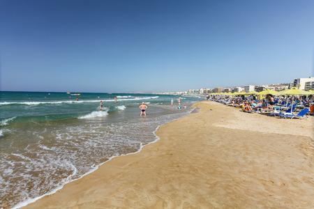 rethymno: Rethymno, Island Crete, Greece, - July 1, 2016: City beach with people and waves of Mediterranean Sea Editorial