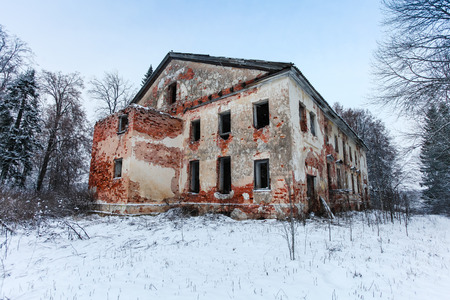 Abandoned and broken old two-storey brick house in the forest, perfect for Halloween