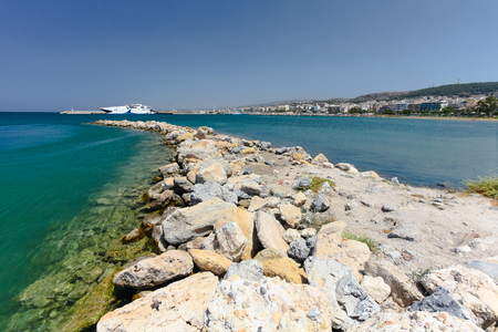View of the artificial cape made from stones and harbor with a big sea liner on the background. Rethymnon is an old historic town on the northern coast of the island Crete.