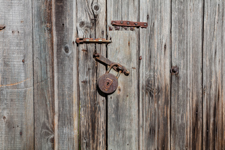 latch: Old rusty padlock and latch on a wooden door with rusty nails