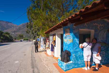 tourists stop: Bali, Island Crete, Greece - June 23, 2016: People buying tickets on the bus and tourists waiting the bus on the bus stop near village Bali to destination Rethymno (Chania) Editorial