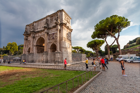 Rome, Italy - September 12, 2016: Tourists visiting The Arch of Constantine (Arco di Costantino), a triumphal arch in Rome, situated between the Colosseum and the Palatine Hill in Rome. Editorial