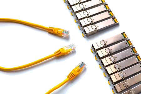 Internet SFP (Small Form-factor Pluggable)  network modules and yellow patch-cords with RJ45 for Lan network . Concept of internet communication and connection. SFP is used for both telecommunication and data communications applications