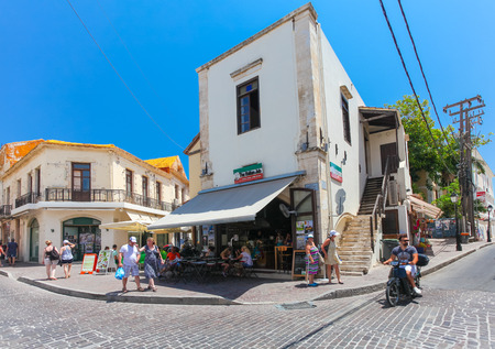 old towns: Rethymnon, Island Crete, Greece, - July 1, 2016: A local citizen on the scooter and tourists are walking on the street and sitting in cafe with Italian food on the street of the old towns part of city Rethymnon Editorial