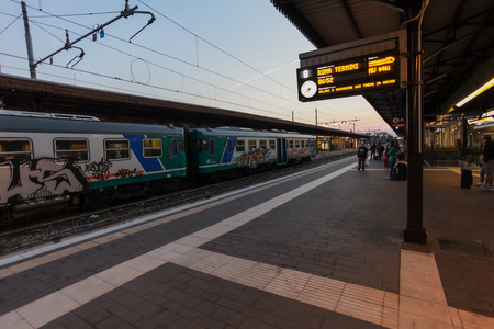 Florence, ITALY- September 10, 2016: Train TrenItalia  of  Regionale type with graffiti on the station in Florence Firenze Campo di Marte and passengers are waiting the high-speed train TrenItalia of  Frecciargento type to Roma (Termini) in the earl Editorial