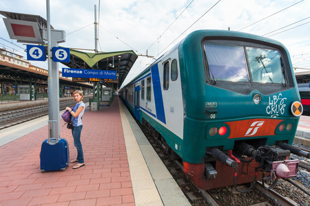 marte: Florence, ITALY- September 10, 2016:Train TrenItalia of  Regionale or Regionale Veloce type on the station in Florence Firenze Campo di Marte and young passenger with blue suitcase.