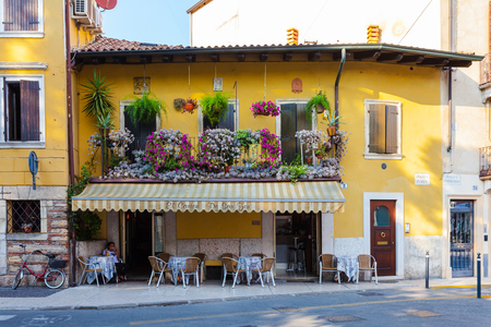 two storey house: VERONA, ITALY- September 08, 2016: Small cafe in old two storey house with beautiful balcony with flowers that is located on Piazza Pizza in Verona