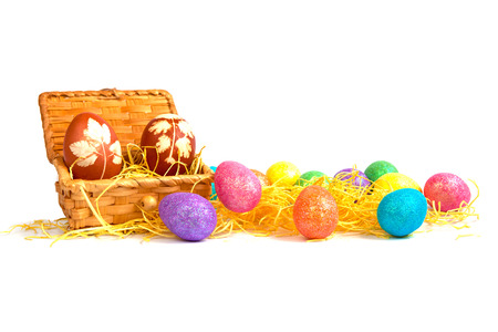 The Easter eggs in the wooden box and colorful Easter eggs near the box in hay. The Easter eggs isolated. Stock Photo