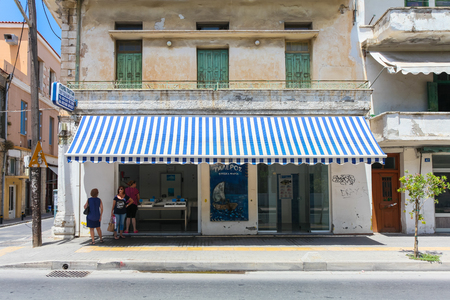 acquirer: Rethymnon, Island Crete, Greece, - July 1, 2016: Local citizens are speaking with each other near fish store with fresh seafood Editorial