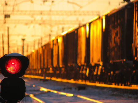 Railway traffic light shows blue signal on railway  and railway with  freight train as the background during sunset. Stock Photo