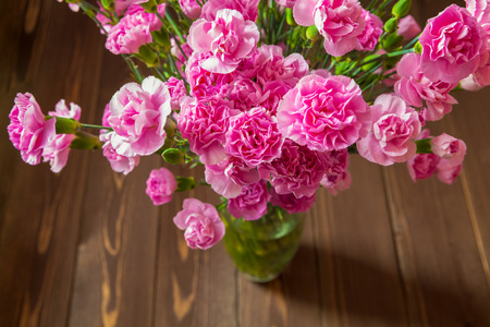 Pink carnations in the vase on the wooden table