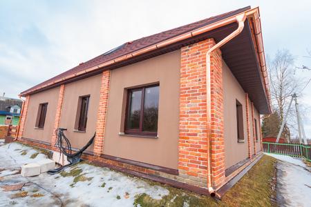La maison moderne avec terrasse est en construction (remodelage) et les matériaux de construction à rénover sont à l'extérieur Banque d'images