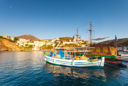 Bali, Island Crete, Greece, - June 24, 2016: Beautiful morning scenery with village Bali, bay of Mediterranean sea and boats of local fishermen and and the big old wooden ship for walking tourists in the sea