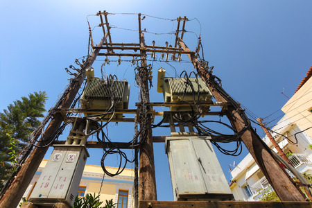 Rethymnon, Island Crete, Greece, - June 23, 2016: High voltage power pole with with a lot of wires and some transformators on the street of part Old Town in Rethymnon.