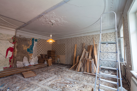 View the vintage room with fretwork on the ceiling of the apartment during under renovation, remodeling and construction. Ladder, garbage of constraction materials and lamp in dark room during of disassembling floors and walls.