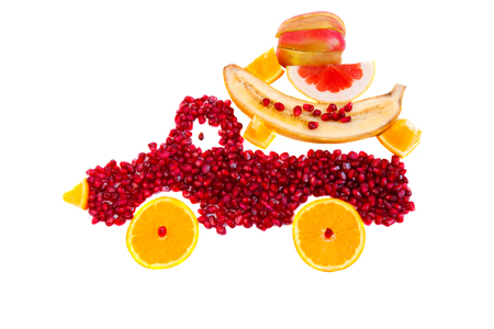Healthy food concept with fruits. Seeds of pomegranate and slices of orange are as shape of lorry with cargo from apple, orange, banana and grapefruit