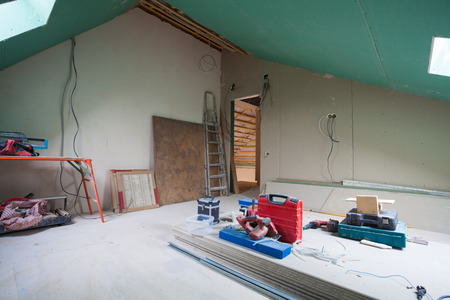 Sheets of drywall, parts of scaffolding, handle tools and construction material in the room of apartment during on the remodeling, renovation and construction