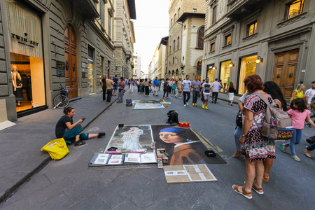 Florence, ITALY- September 11, 2016: Street painters have painted famous pictures of masterpiece on the road of street and in this  way they are earning money
