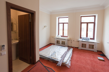 Construction materials,  furniture  and phone  are on the floor of apartment in the hotel during under renovation, remodeling and construction.