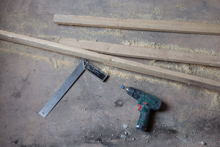wood floor: Electric perforator with drill is on the dirty and dusty wooden floor during under renovation, remodeling and construction of apartment.