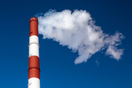 Heat and power central, smoke industrial chimney  against clear blue sky
