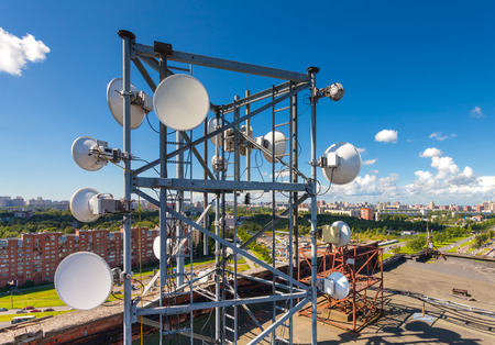 Telecommunication tower with TV antennas, satellite dish, microwave and panel antennas of mobile operators is located on the roof and city landscape as background Stock Photo