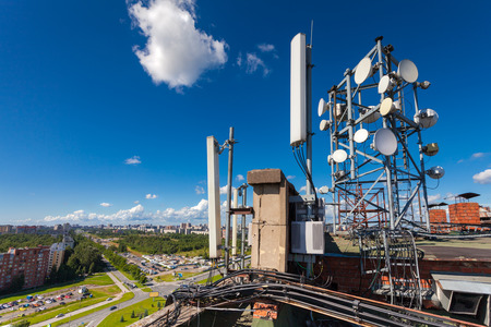 Telecommunication tower with wireless communications systems are including microwave, panel antennas, fider,  optic and power cables of mobile operators are located on the roof and city landscape as background. Outdoor equipment of basic station.