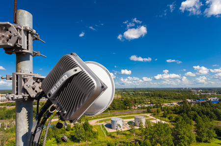 Part of telecommunication tower with outdoor unit of wireless communications system is including microwave antenna, optic and power cables are located on the roof and city landscape as background. Outdoor unit of equipment of basic station.