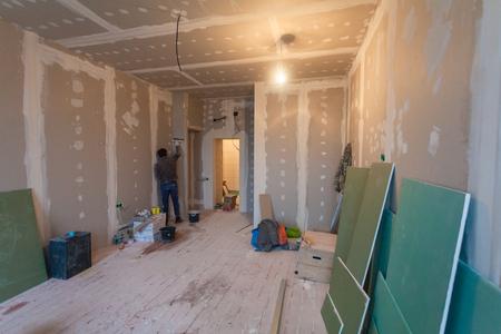Werknemer bereidt muren voor op verbouwing het door gipsplaat (plasteboard, gips) en interieur van appartement met materialen tijdens de renovatie en bouw.