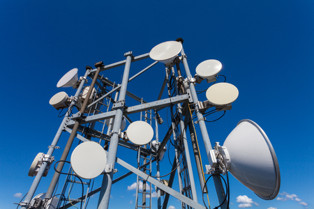 Telecommunication tower with microwave antennas and satellite dishes with cables and fiber optic  against blue sky Stock Photo