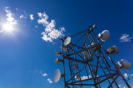Telecommunication tower with microwave, radio antennas and satellite dishes with shadows on the roof  against blue sky and sun
