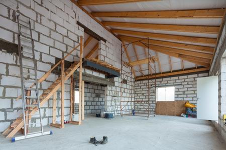 Escalera, partes de andamios y material de construcción en el piso durante la remodelación, renovación, extensión, restauración, reconstrucción y construcción