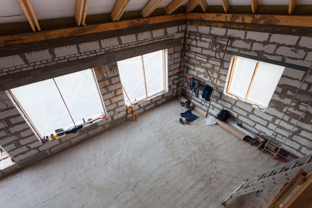 Workers clothes, parts of scaffolding and construction material on the floor during on the remodeling, renovation, extension, restoration, reconstruction and construction