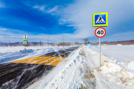 Dangerous snowing road with crosswalk, bus stop and road signs for driving cars and public transport during  blizzard or  snowstorm. Stock Photo