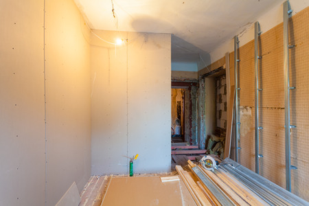 Interior of upgrade apartment with materials during on the remodeling, renovation, extension, restoration, reconstruction and construction. ( making wall from gypsum plasterboard) 免版税图像