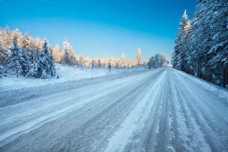 Empty winter road  with ice-slick and snow through snowy fields and forest