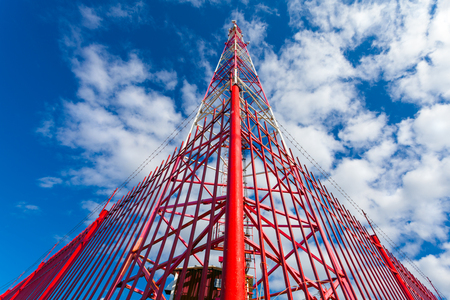 Telecommunication tower with panel antennas and radio antennas and satellite dishes for mobile communications (2G, 3G, 4G, 5G) with red fence around tower against blue with clouds Stok Fotoğraf