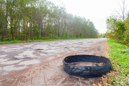 Destroyed rubber car tire car on rural bumpy broken road Stock fotó