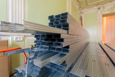 Frames for plasterboard (metal profiles for drywall) are being prepared for making gypsum walls by workers in an apartment is under construction, remodeling, renovation, extension, restoration, reconstruction, upgrade.