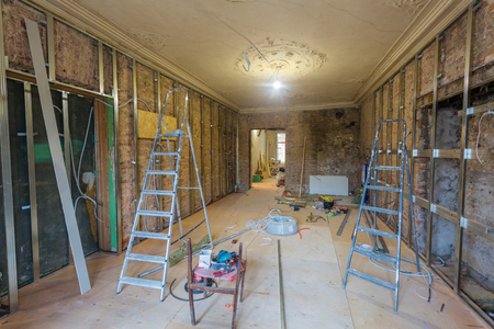 Working process of installing metal frames for plasterboard (drywall) for making gypsum walls with ladders and tools in apartment is under construction, remodeling, renovation, extension, restoration and reconstruction