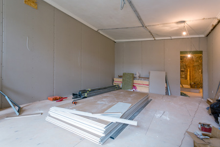 Working process of installing metal frames for plasterboard (drywall) for gypsum walls and tools in apartment is under construction, remodeling, renovation, extension, restoration and reconstruction. Banque d'images