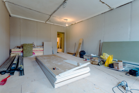 Working process of installing metal frames for plasterboard (drywall) for gypsum walls and tools in apartment is under construction, remodeling, renovation, extension, restoration and reconstruction. Stock Photo