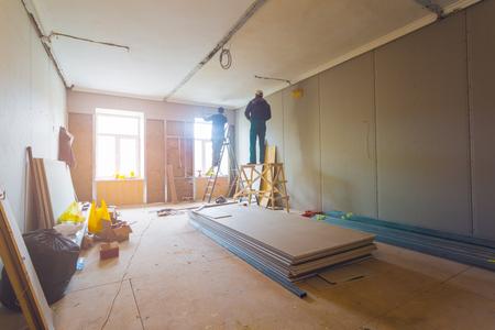 Der Arbeitsprozess der Installation von Metallrahmen für Gipskartonplatten (Trockenbau) zur Herstellung von Gipswänden mit Leiter und Werkzeugen in der Wohnung ist im Aufbau, Umbau, Renovierung, Erweiterung, Restaurierung und Wiederaufbau
