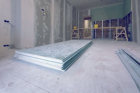 Working process of installing metal frames and plasterboard (drywall) for gypsum walls and materials are in apartment is under construction, remodeling, renovation, extension, restoration and reconstruction