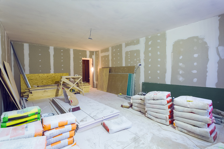 Materials for constraction (putty packs, sheets of plasterboard or drywall)  in apartment is under construction, remodeling, renovation, extension, restoration and reconstruction. Stock Photo - 97581648