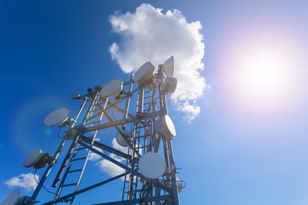 Telecommunication tower with TV antennas, satellite dish, microwave and panel antennas of mobile operator against blue sky and sun Stock Photo