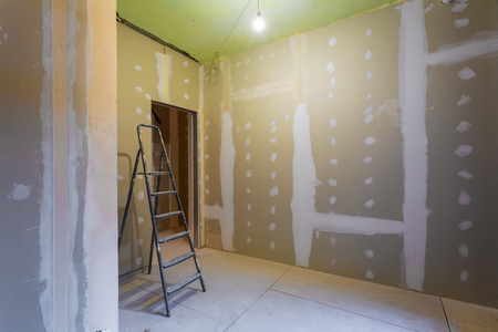 Ladder and room interior with plasterboard drywall for gypsum walls prepared to painting in apartment is under construction, remodeling, renovation, extension, restoration and reconstruction. Standard-Bild