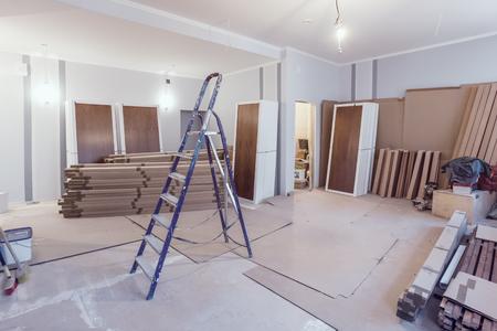 Interior del apartamento durante la construcción, remodelación, renovación, extensión, restauración y reconstrucción: escalera y materiales de construcción en la habitación Foto de archivo