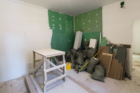 Wooden board in room, sheets of plasterboard or drywall and construction garbage in the bags are an apartment during on the construction, remodeling, rebuilding and renovation. Stock Photo