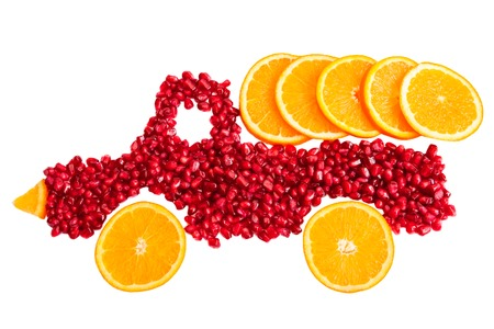 Healthy food concept with fruits. Seeds of pomegranate and slices of orange are as shape of lorry with cargo of orange